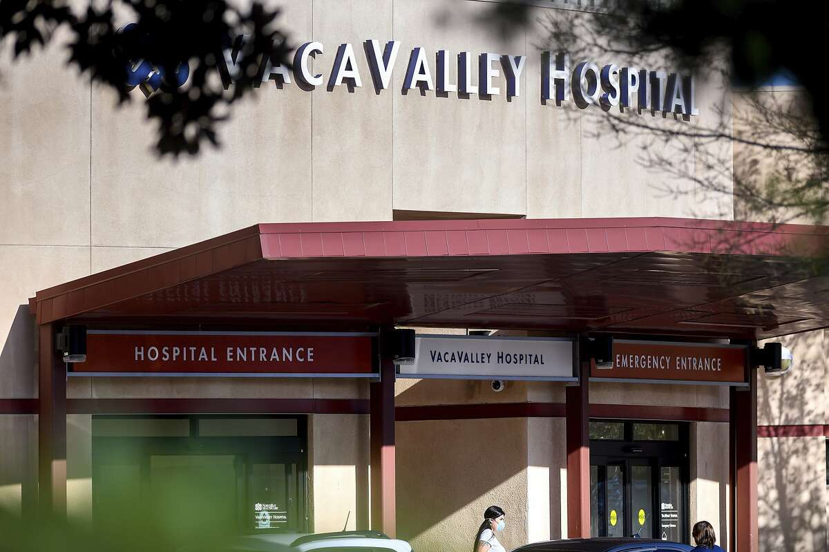 A person leaves NorthBay VacaValley Hospital, where a woman diagnosed with coronavirus previously sought treatment, on Thursday, Feb. 27, 2020, in Vacaville, Calif. Public health officials are retracing the steps of the woman, believed to be the first person in the U.S. to contract the highly contagious coronavirus without traveling abroad or coming in close contact with an international traveller. (AP Photo/Noah Berger)