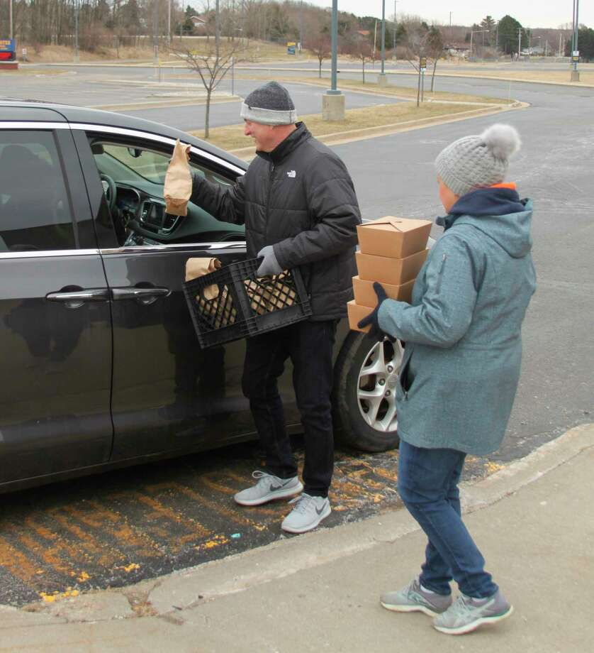 Manistee Middle/High School principal Andy Huber serves up a breakfast and lunch to someone while MAPS food service director Keri Carlson brings more. (Ken Grabowski/News Advocate)