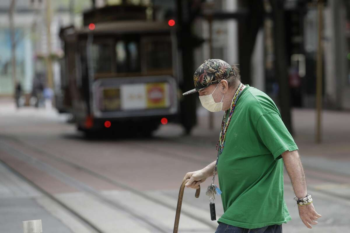 A man wears a mask while crossing a street in front of a Cable Car in San Francisco, Sunday, March 15, 2020. (AP Photo/Jeff Chiu)