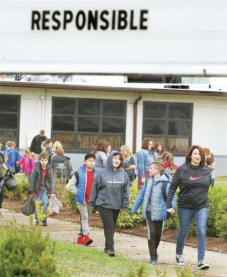 "Students head home Monday afternoon from Central Elementary School in Roxana and walk past a school sign saying the character word for the week is ""Responsible."" Most health officials believe closing schools across Illinois by Gov. J.B. Pritzker until at least March 30 is the responsible thing to do to slow the spread of the COVID-19 virus."