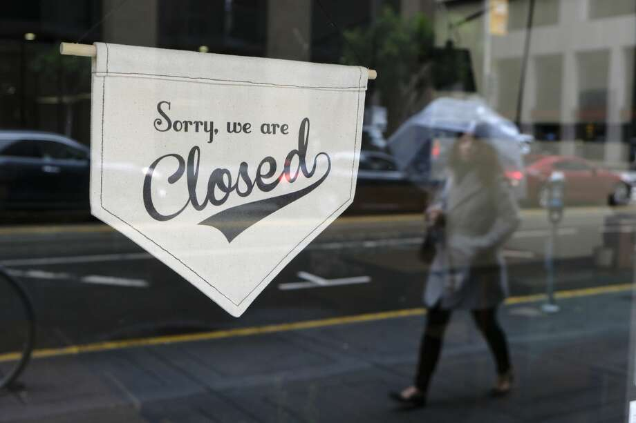 A woman walks along through the Financial District past the closed Homage Ltd. restaurant which is normally open for breakfast and lunch Monday, March 16, 2020, in San Francisco. Millions of California's oldest and youngest residents stayed home Monday as officials took increasingly strident steps to separate people and contain the spread of the coronavirus. Evidence that people were staying home included traffic flowing freely on some freeways that are normally congested during rush hours.(AP Photo/Eric Risberg) Photo: Eric Risberg/AP