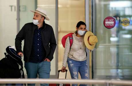 A man and a woman wear face masks amid fear of the new coronavirus while exiting the international terminal at George Bush Intercontinental Airport on Thursday, March 12, 2020, in Houston.