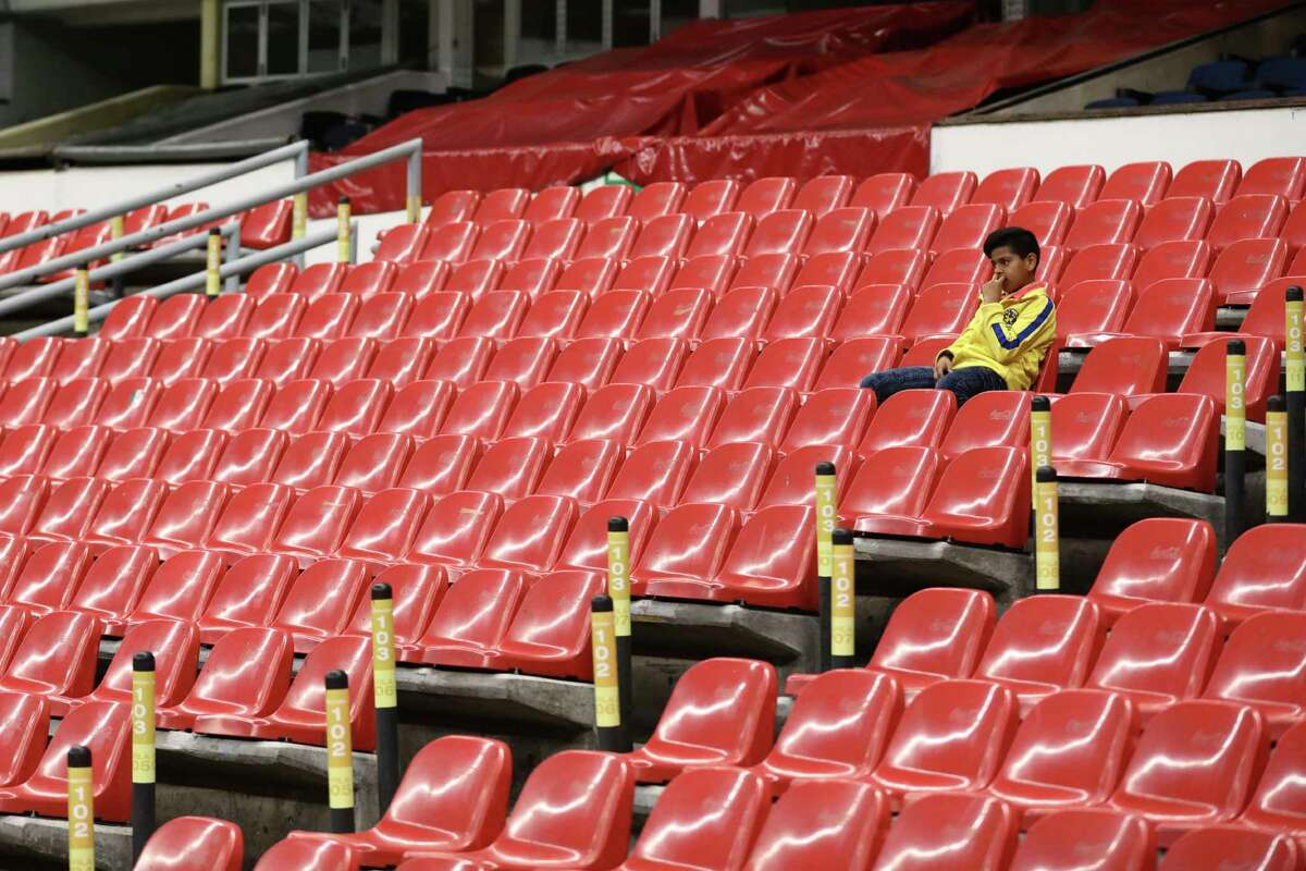 A boy sits on the stands prior to a Mexican soccer league match between America and Cruz Azul at Azteca stadium in Mexico City, Sunday, March 15, 2020. The match was played behind closed doors as a precaution against the spread of the new coronavirus. (AP Photo/Eduardo Verdugo)