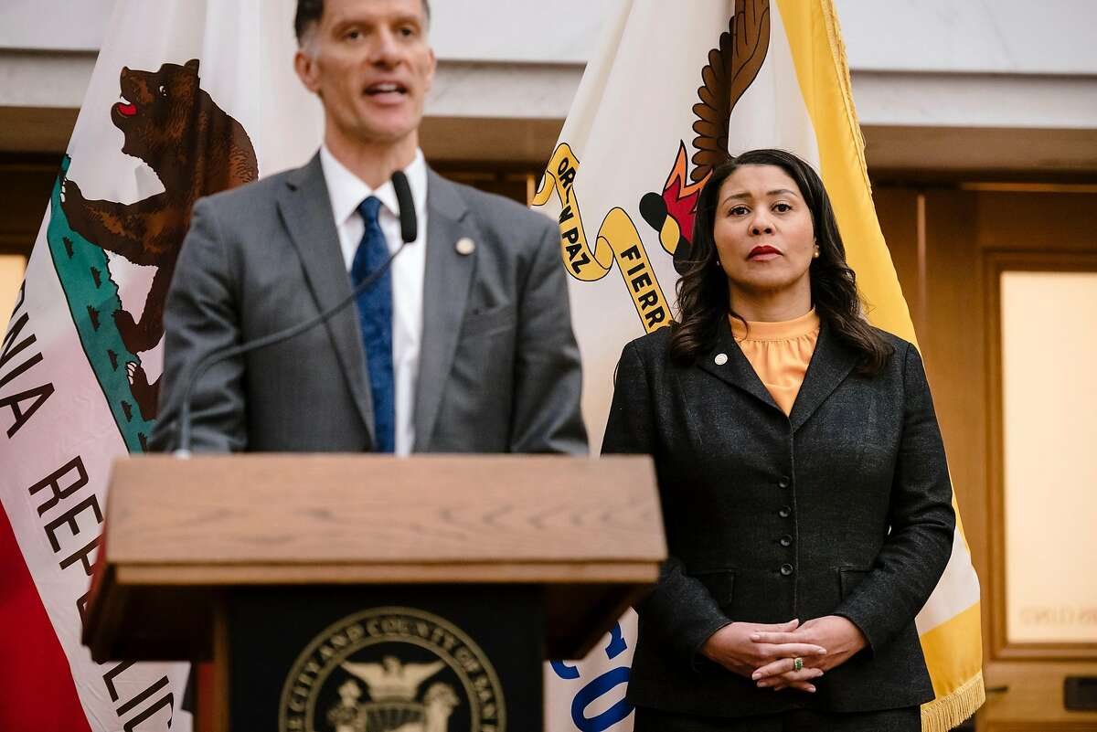 Mayor London Breed, right, listens as SF Public Health Officer Dr. Grant Colfax speaks about the announcement the city and county of San Francisco has issued a public health order requiring that residents remain in place, with the exception being for essential needs only, in response to the heightened threat of the Coronavirus, during a press conference at City Hall in San Francisco, California, US, on Monday, March 16, 2020.