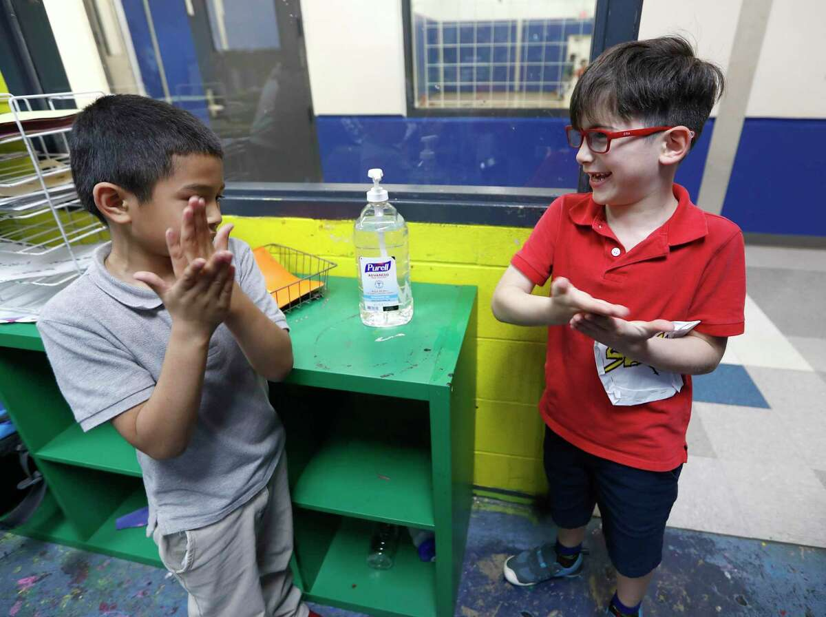 Victor Parache, 6, left, and Emiliano Arango, 7, use the hand sanitizer at the Heights Boys and Girls Club, in Houston,Thursday, March 12, 2020. Houston and Harris County on Monday launched a service to connect essential workers with child care.