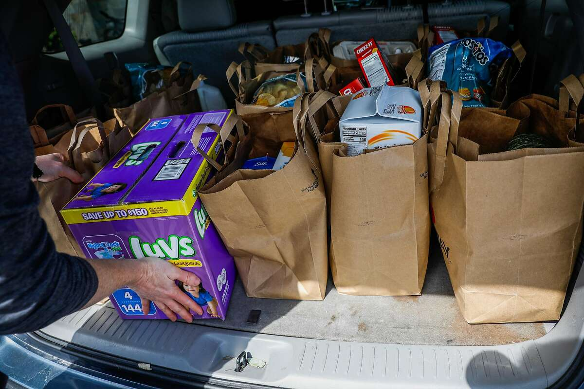 Chris Morgan loads up his car full of groceries for his family of four outside Safeway after Mayor London Breed announced that six Bay Area counties would lockdown non-essential services due to the coronavirus on Monday, March 16, 2020 in San Francisco, California.