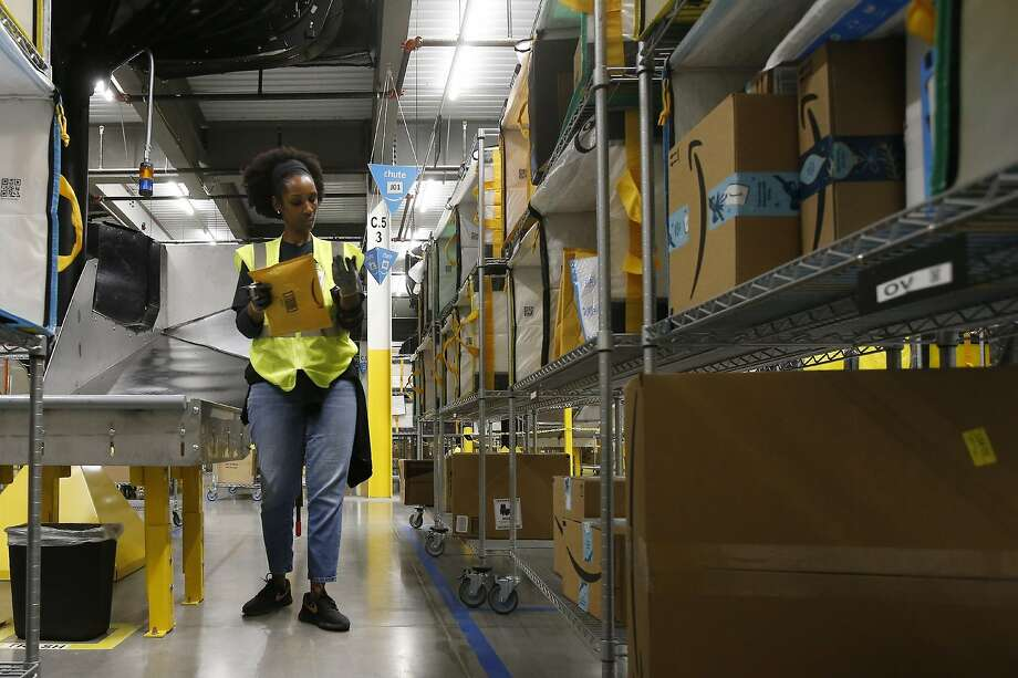 FILE - In this Dec. 17, 2019, file photo, Tahsha Sydnor stows packages into special containers after Amazon robots deliver separated packages by zip code at an Amazon warehouse facility in Goodyear, Ariz. On Monday, March 16, 2020, Amazon said that it needs to hire 100,000 people across the U.S. to keep up with a crush of orders as the coronavirus spreads and keeps more people at home, shopping online. (AP Photo/Ross D. Franklin, File) Photo: Ross D. Franklin / Associated Press 2019