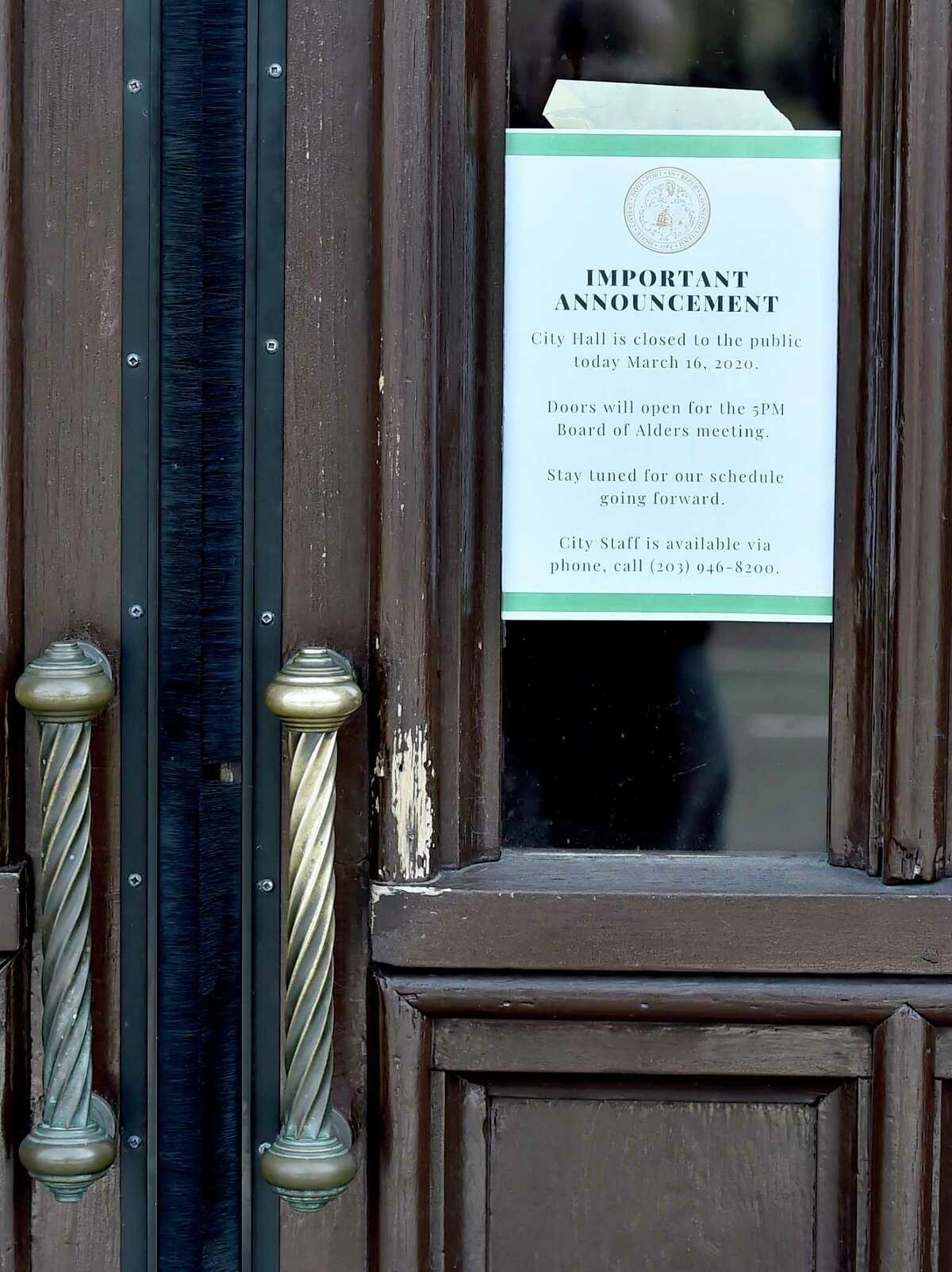 New Haven, Connecticut - Friday, March 16, 2020: A sign on the front doors announces the closing of New Haven City Hall amidst the public health concern over the Coronavirus / COVID-19 outbreak.
