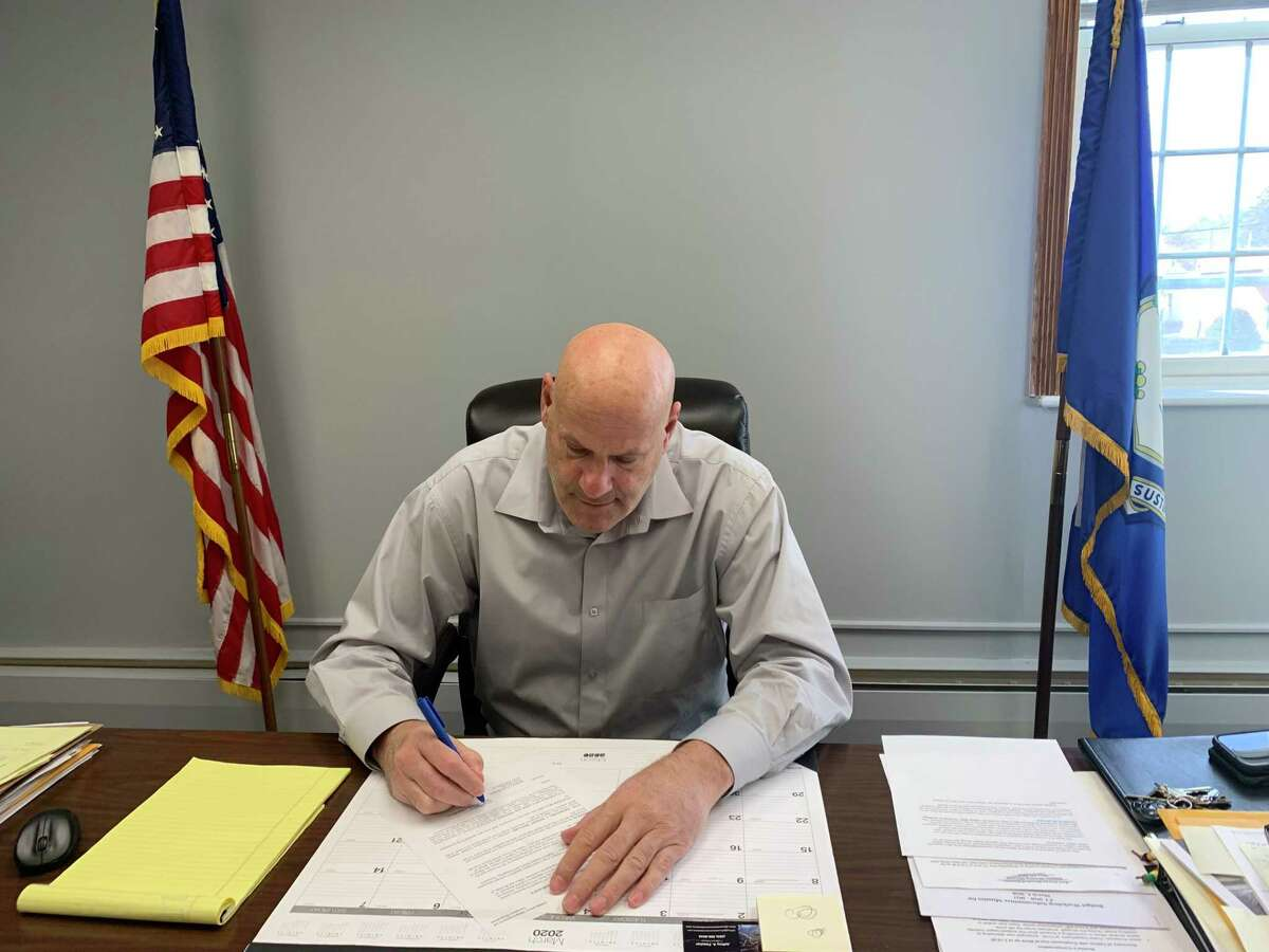 """East Haven Mayor Joe Carfora signs the COVID-19 """"State of Emergency"""" declaration on Monday, March 16, 2020."""