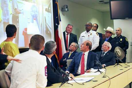Officials view a video presentation about the drive through testing operations as Gov. Greg Abbott speaks at the San Antonio Operations Center on March 16, 2020.