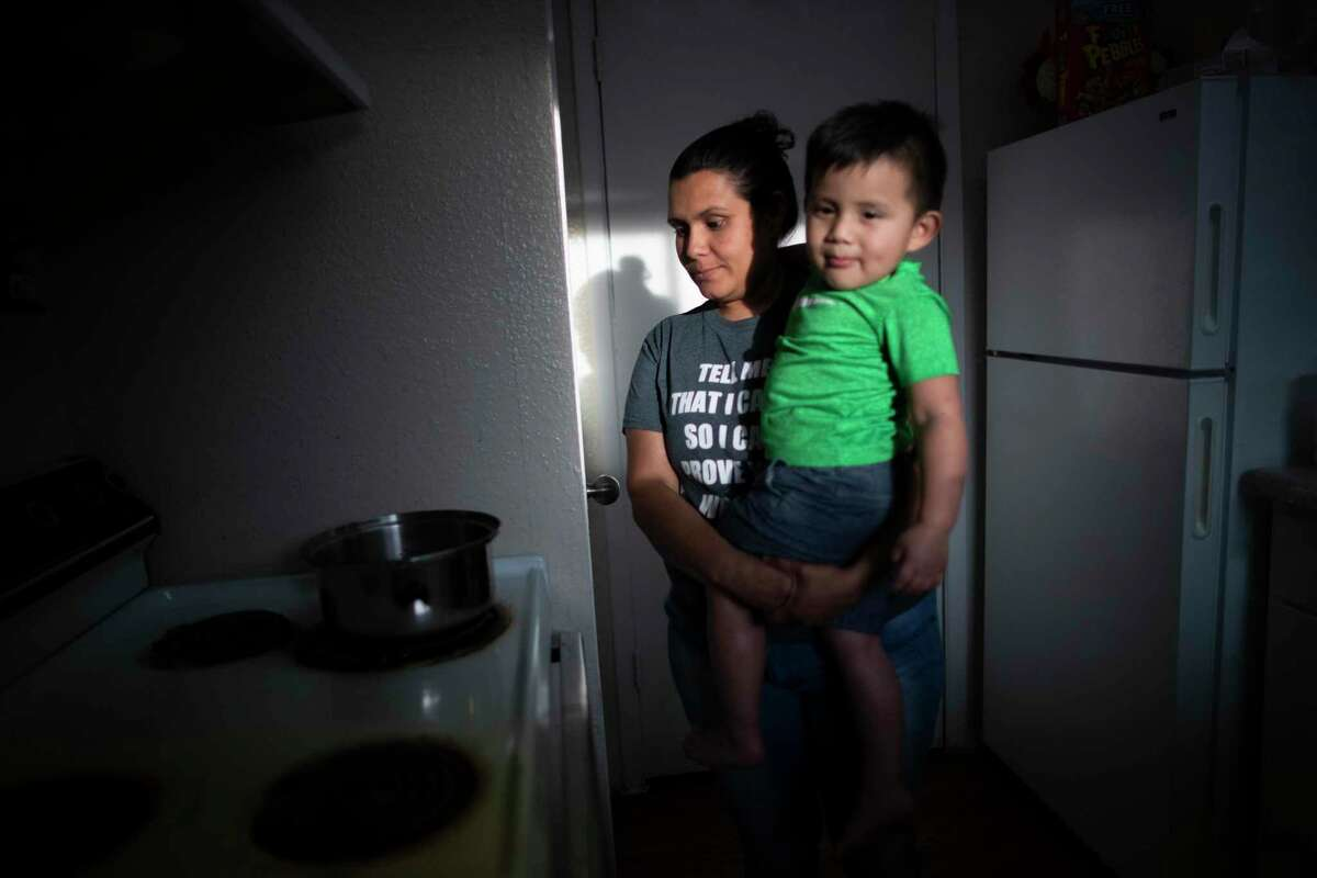 Lurvin Perdomo, 35, prepares tea while holding her son Carlos A. Rodríguez, 2, who has been coughing at their home on Thursday, March 12, 2020, in Houston. Perdomo is concerned about the lack of access to medicines and supplies that could help her family stay healthy during the uncertainty that has brought the COVID-19 crisis.