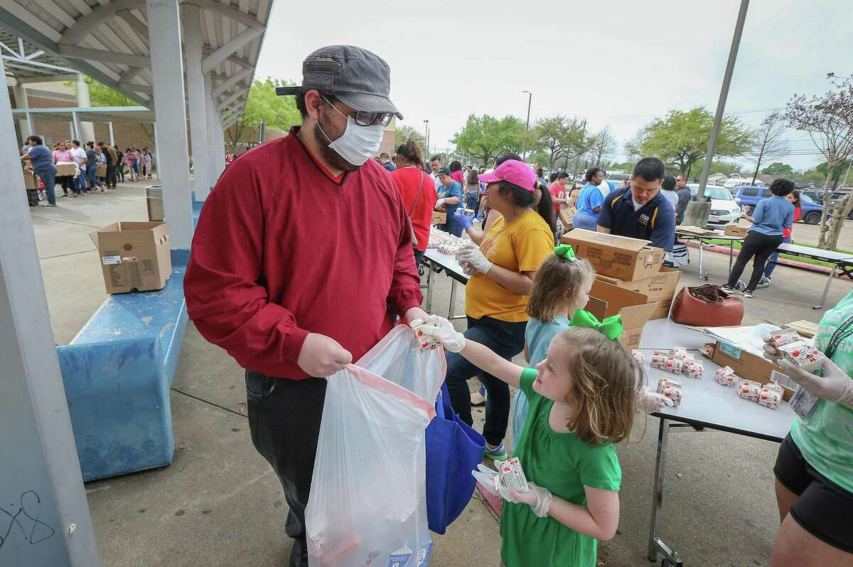 Haryie Garrigues wears a protective mask as he get drinks from 5-year-old Eleanor Hutcheson as the Houston Independent School District along with the Houston Food Bank handed out food to hundreds of families in need Saturday, March 14, 2020, in Houston.