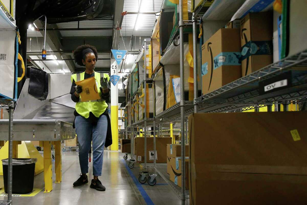 FILE - In this Dec. 17, 2019, file photo, Tahsha Sydnor stows packages into special containers after Amazon robots deliver separated packages by zip code at an Amazon warehouse facility in Goodyear, Ariz. On Monday, March 16, 2020, Amazon said that it needs to hire 100,000 people across the U.S. to keep up with a crush of orders as the coronavirus spreads and keeps more people at home, shopping online. (AP Photo/Ross D. Franklin, File)