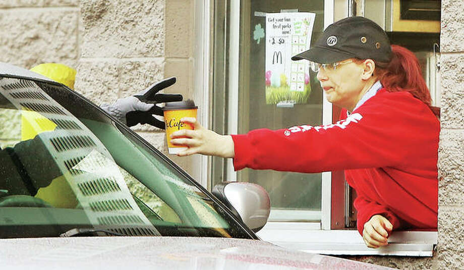 A gloved hand reaches out Monday to accept a coffee at the downtown Alton McDonald's restaurant's drive-through window. Starting Tuesday, only drive-through and carry-out meals can be served after Gov. J.B. Pritzker ordered dine-in areas of restaurants and bars closed throughout the state.