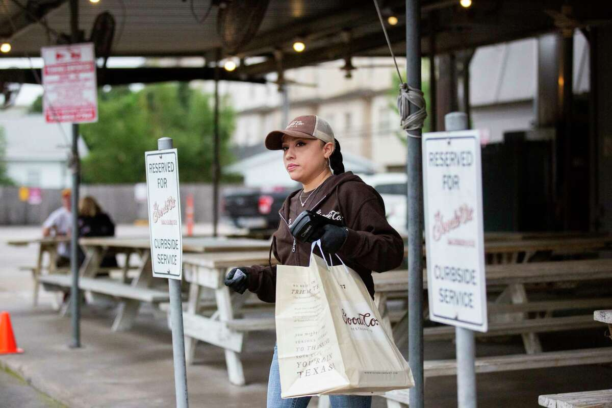 Goode Co. employee Brenda Hernandez walks out of restaurant on Monday, March 16, 2020, in Houston with a carry-out order for a customer.