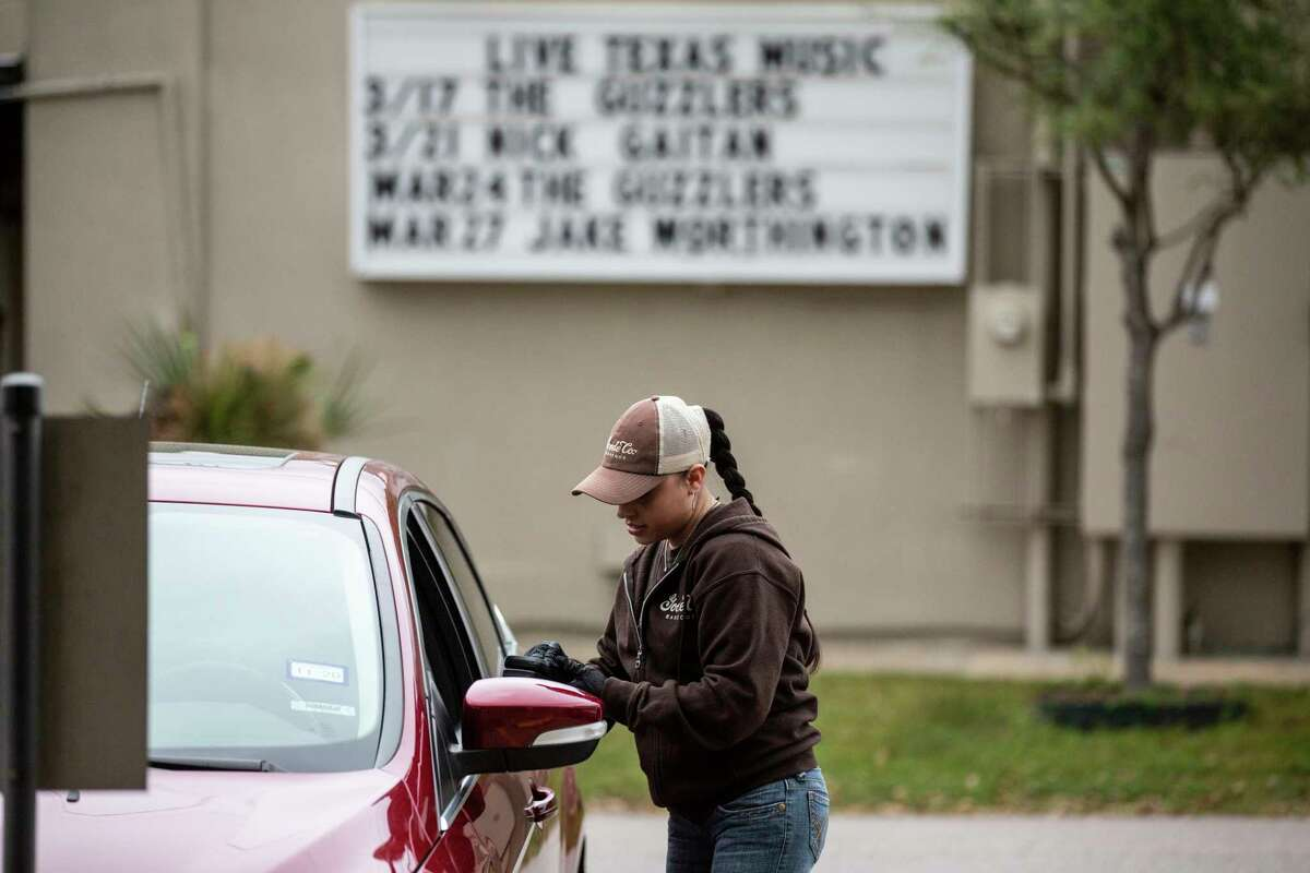 Goode Co. employee Brenda Hernandez finishes a carry-out transaction on the curbside of the restaurant on Monday, March 16, 2020, in Houston.