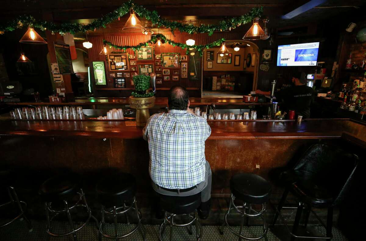 A man sits a the bar inside Kenneally's Irish Pub on Monday, March 16, 2020, in Houston. City officials, starting tomorrow morning, ordered the closure of bars and limited restaurants to only fill drive through or pickup orders for 15 days, in response to the new coronavirus pandemic.