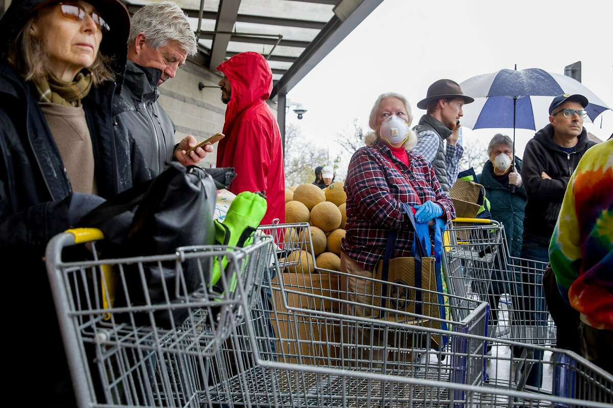 """Sam Herbert of Berkeley wears a face mask and gloves as she waits in line with dozens of others to enter Berkeley Bowl in Berkeley Bowl, Calif. Saturday, March 14, 2020. Stores across the Bay Area have been overwhelmed with shoppers """"panic buying"""" amid the thread of the Coronavirus and increased self-isolation within communities."""