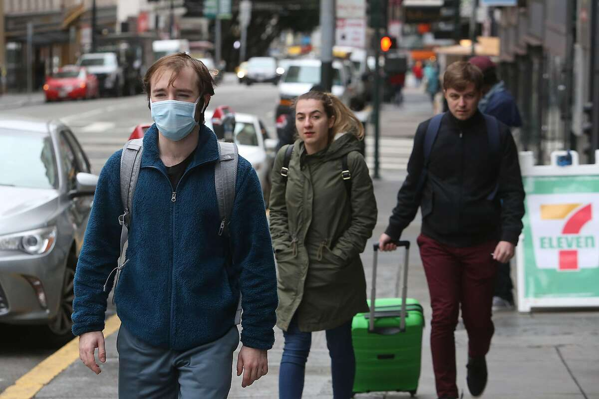 Dave McFall of San Francisco, wears a mask as he walks to work along Sutter Street on Monday, March 16, 2020 in San Francisco, Calif.