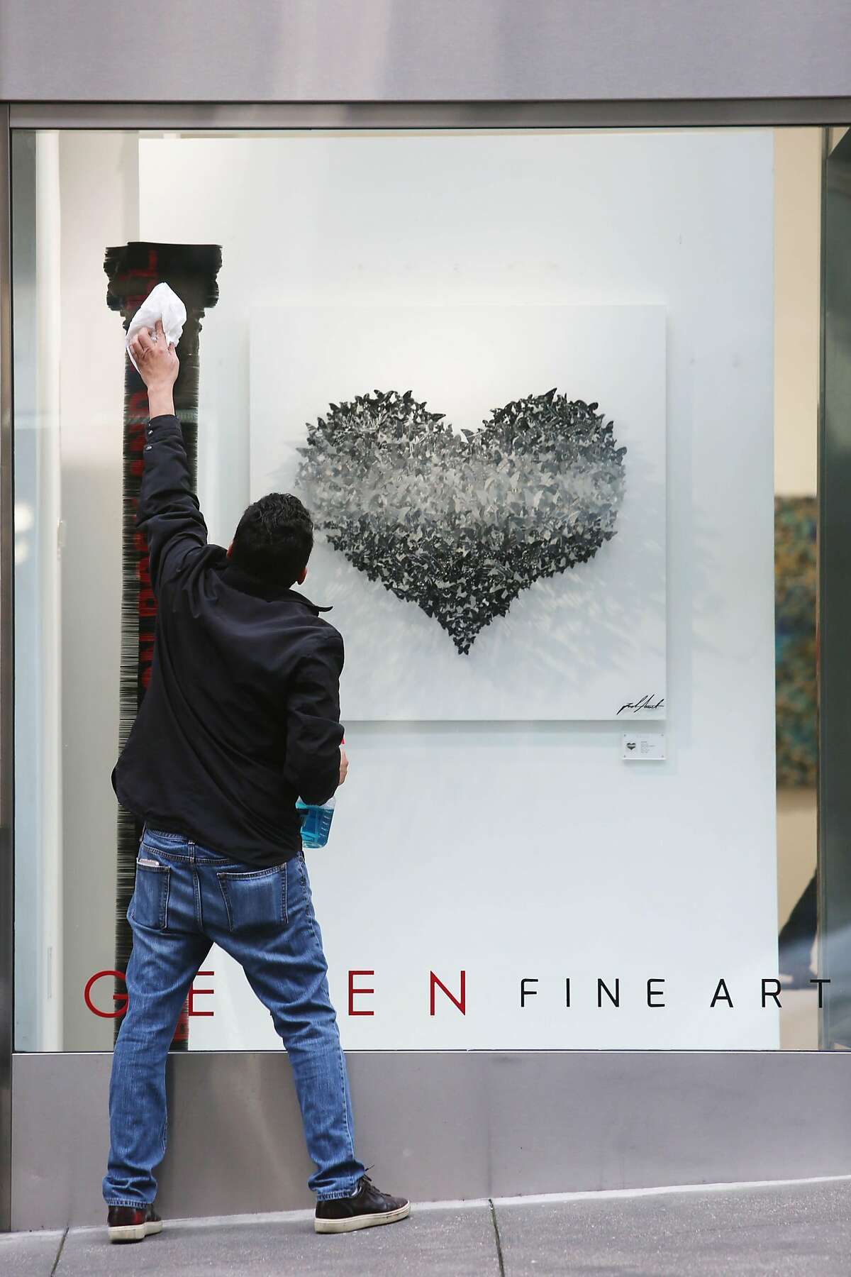 A man cleans the windows outside of Gefen Fine Art on Monday, March 16, 2020 in San Francisco, Calif. Bui said business has been slow for two weeks.