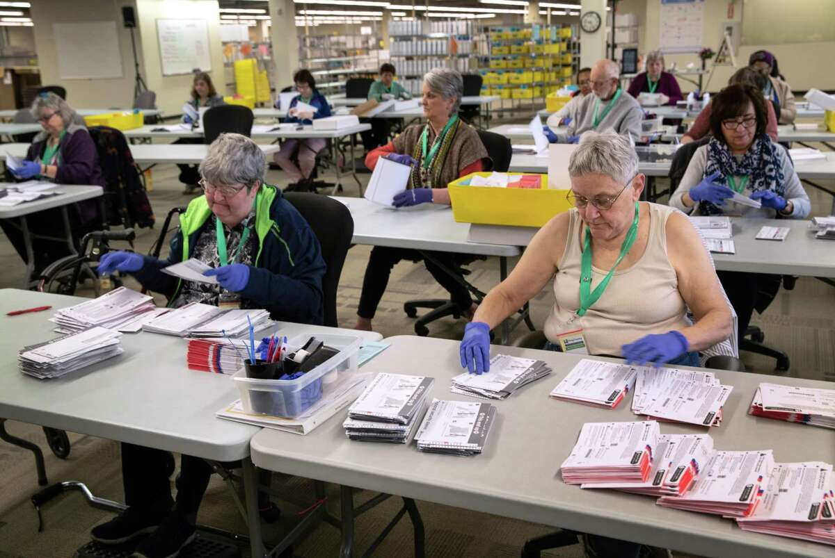 Election workers wearing protective gloves sort through mailed-in ballots at the King County Elections ballot processing center on March 9, 2020, in Renton, Washington. Election officials mandated wearing gloves in this year's primary election counting process, as a protective measure. King County has had the highest number of deaths in the U.S. due to the coronavirus outbreak.