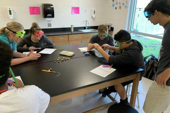 Debra Nolte's Hargrave High School AP Chemistry students teach a lesson to Huffman Middle School eighth graders on Oct. 15