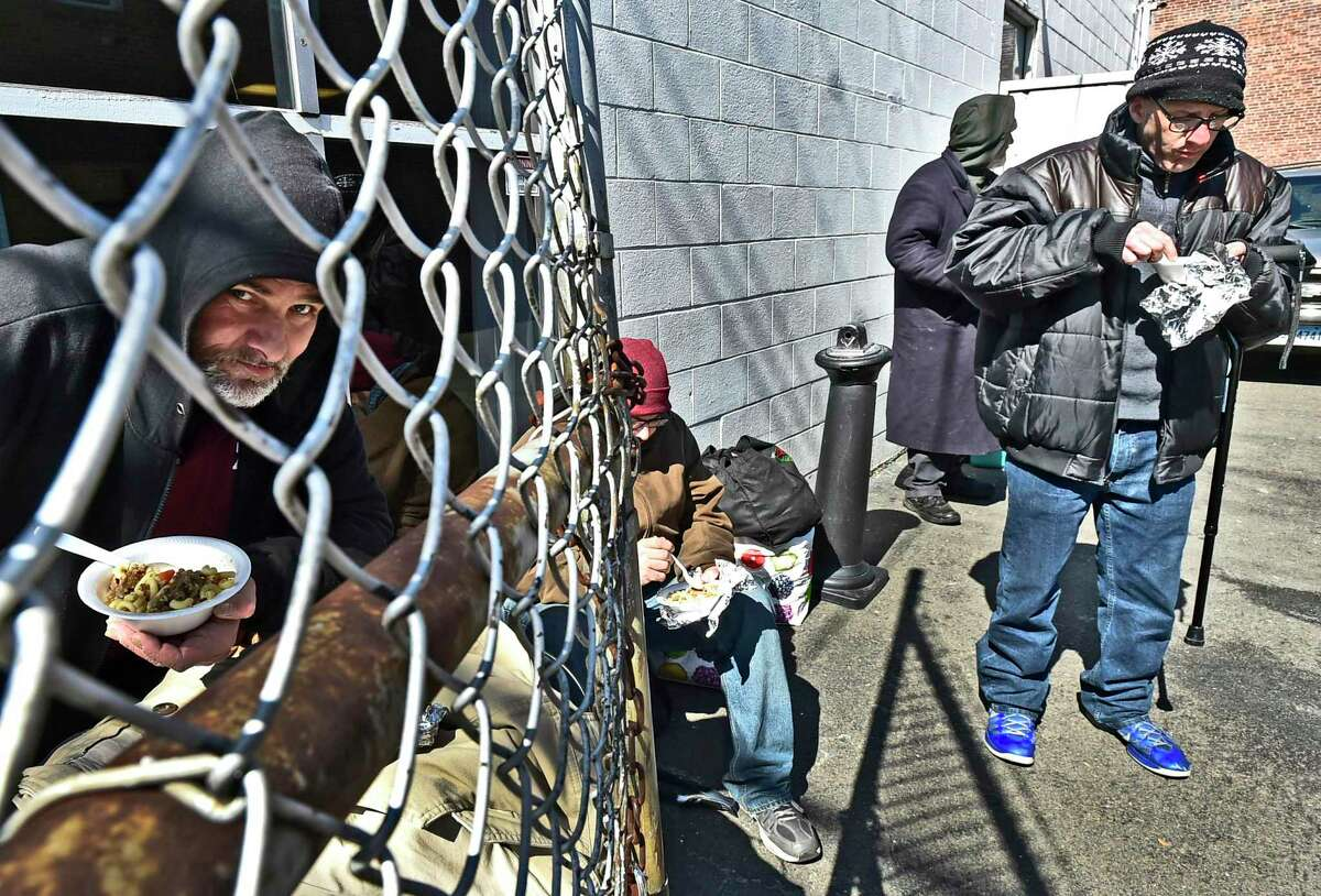 New Haven, Connecticut - Friday, March 16, 2020: Raymond Brown, left, who spent the night at the emergency overflow homeless shelter, left, eats a