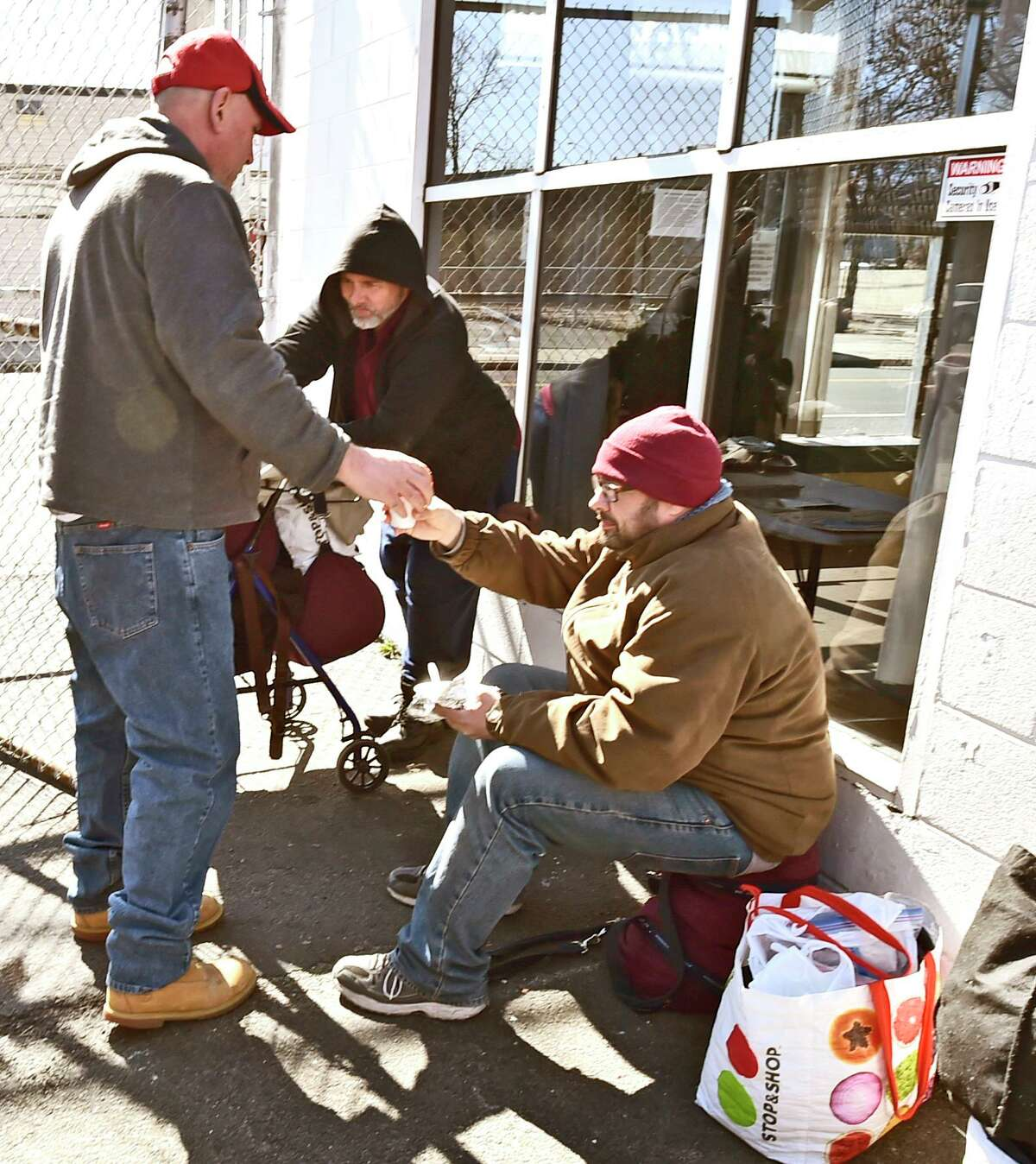 New Haven, Connecticut - Friday, March 16, 2020: Mike Grillo of the 18-month program discipleship program of the 180 Center of New Haven homeless ministry on Grand Avenue in New Haven, left, distributes coffee outside to those who received a a