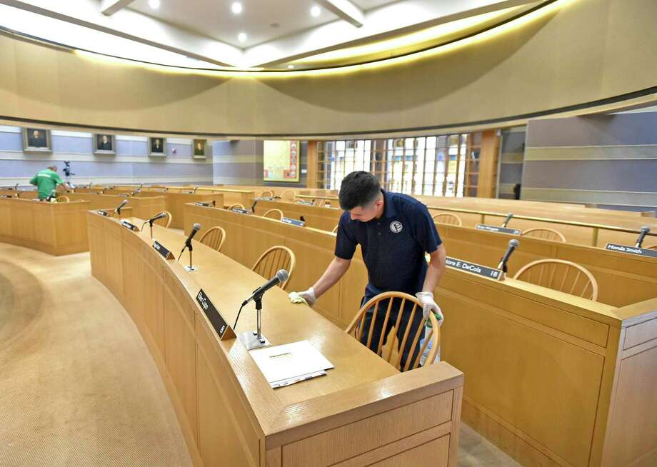 Byron Machic, right, and Donny Grande of Performance Environmental Services disinfect aldermanic chambers st New Haven City Hall recently. Photo: Peter Hvizdak / Hearst Connecticut Media / New Haven Register