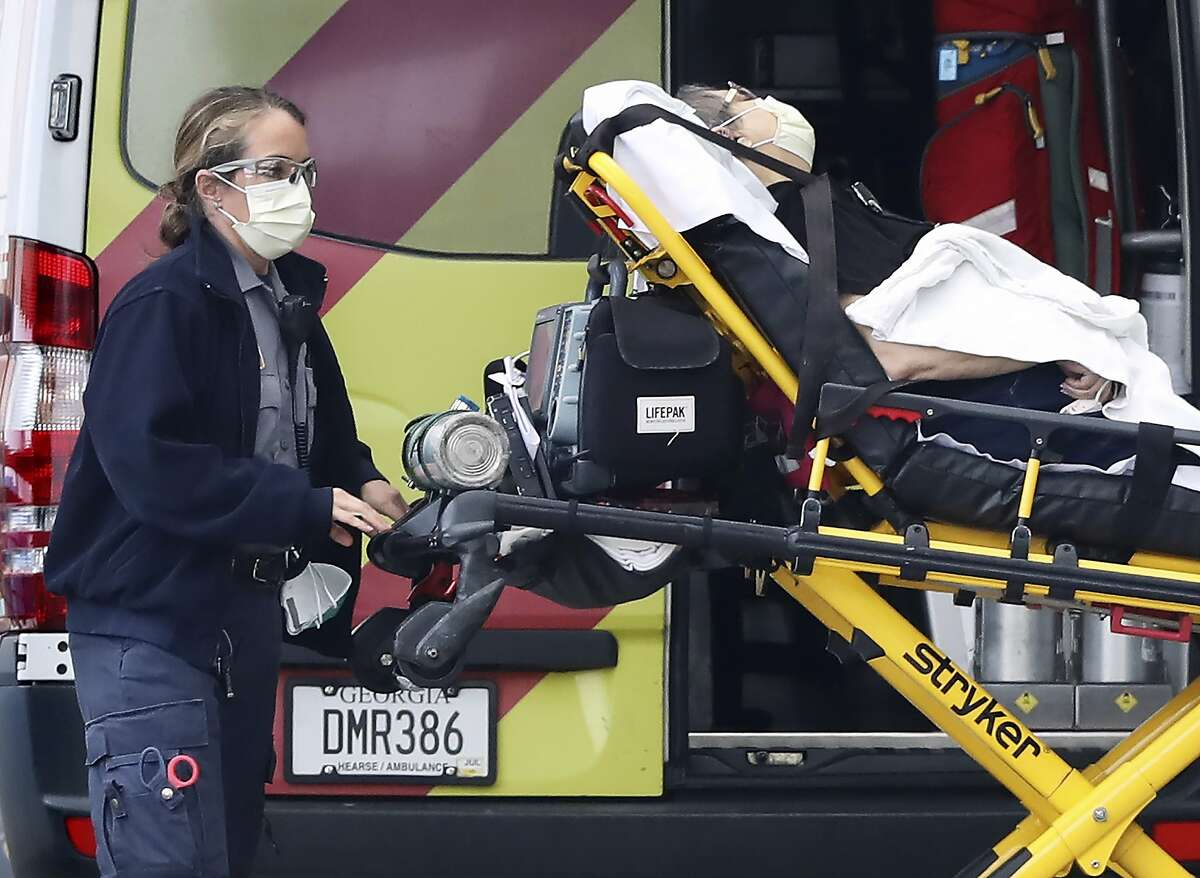 """An ambulance worker and a patient wear masks, arriving at the emergency entrance at WellStar Kennestone Hospital on Monday, March 16, 2020, in Marietta, Ga. Georgia authorities confirmed the state's first coronavirus-related death at WellStar Kennestone Hospital last Thursday saying the victim, who tested positive for the COVID-19 illness on March 7, also had """"underlying medical conditions."""" (Curtis Compton/Atlanta Journal-Constitution via AP)"""