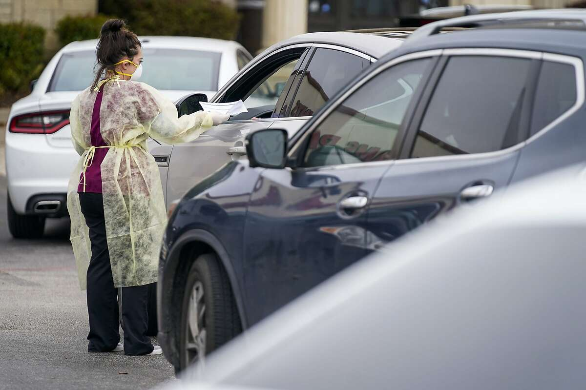 Office manager Kristy Castillo talks with a patient as cars line up for drive-thru coronavirus testing at Neighborhood Medical Center on Monday, March 16, 2020, in Dallas. Patients first were tested for flu and streptococcal infections at the center. (Smiley N. Pool/The Dallas Morning News via AP)
