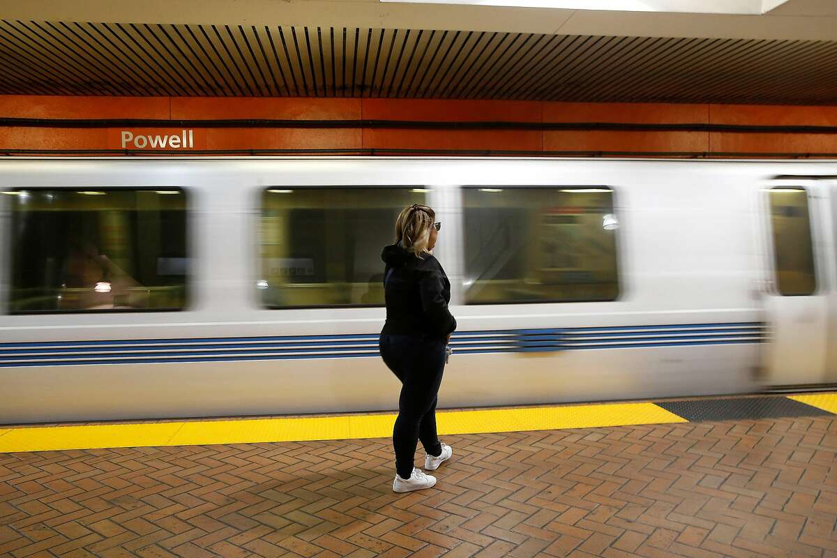 Yulet Pina of San Francisco waits on the platform as a BART train arrives at Powell Street Station on Monday, March 16, 2020 in San Francisco, Calif.
