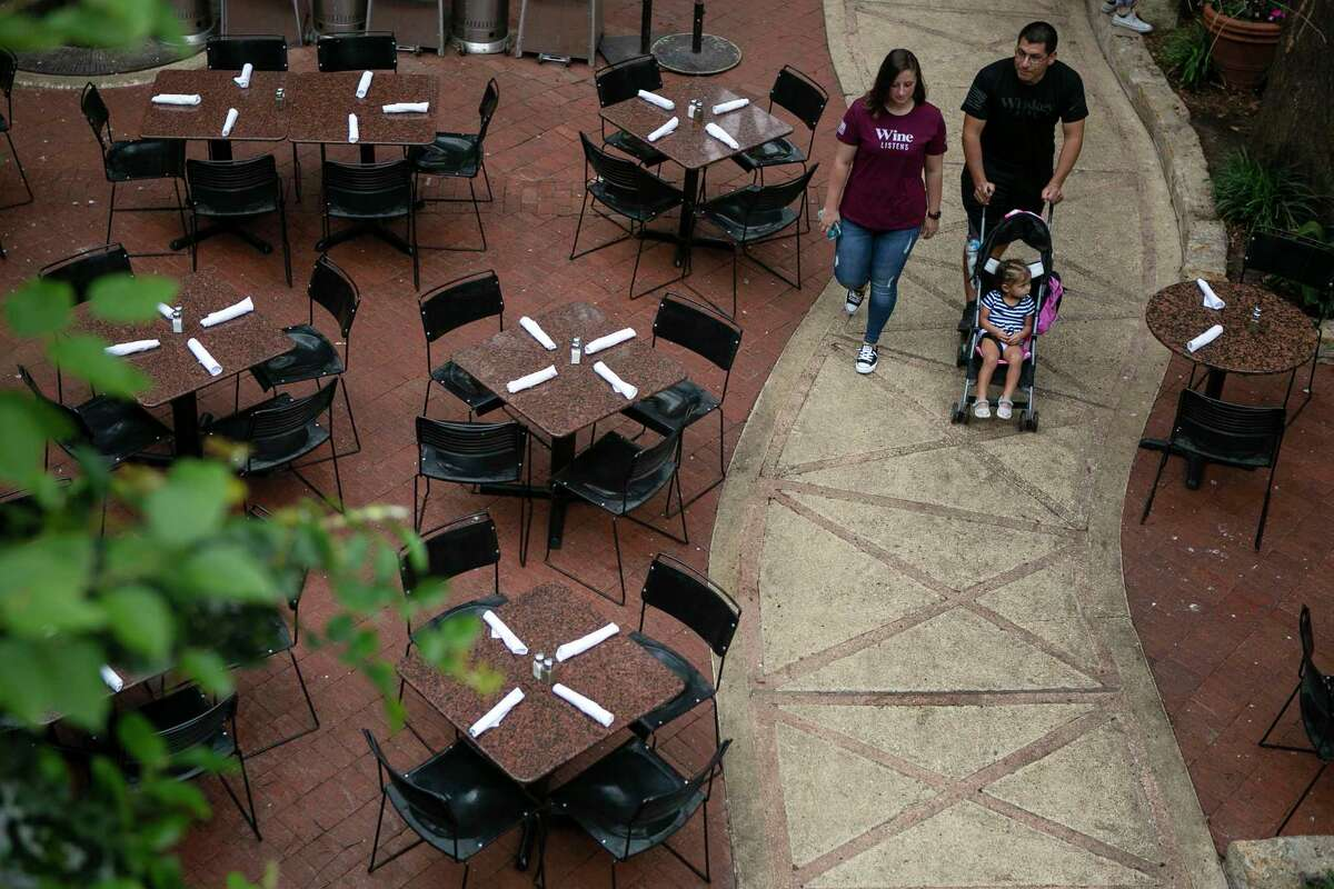 People stroll between empty tables at Paesano's on the River Walk in San Antonio on March 16, 2020.