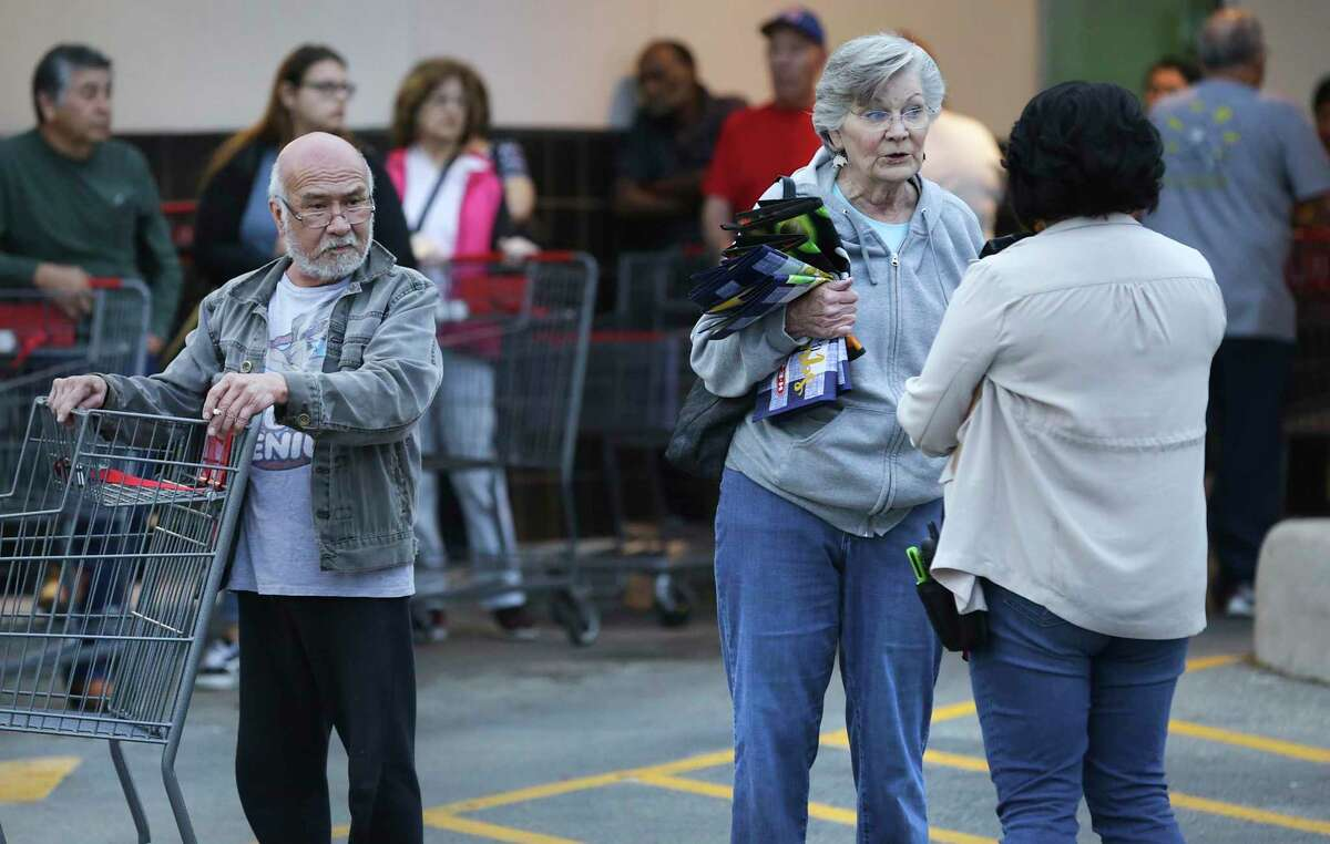 Tanya Evers, second from right, talks with an employee at the Deco District H-E-B as shoppers line up early to be the first ones in the store on Monday, March 16, 2020. Evers said she usually shops every Monday about 7 a.m. for her weekly grocery needs, not panic buying. She was going to return later in the day to get the items she needs.