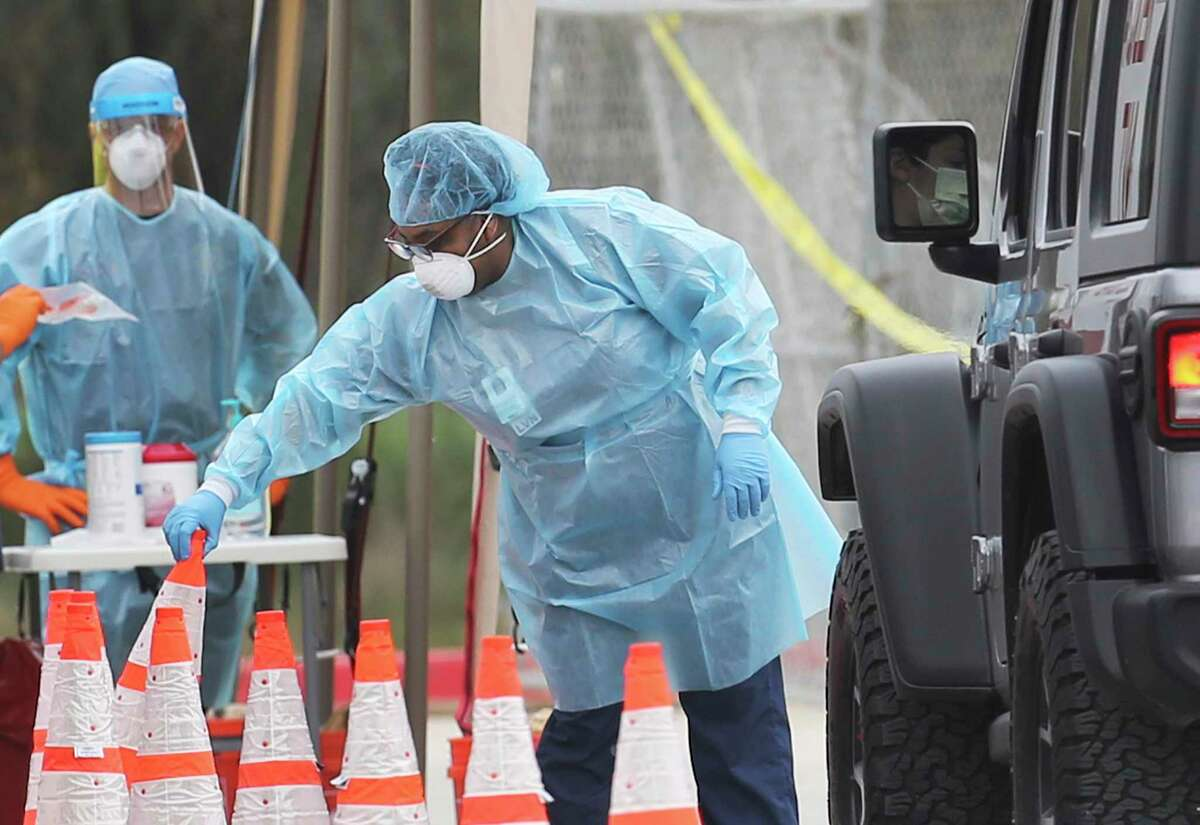 Medical personnel prepare to take a test sample from a person at the drive-through coronavirus testing center in the Medical Center area on Monday, March 16, 2020.