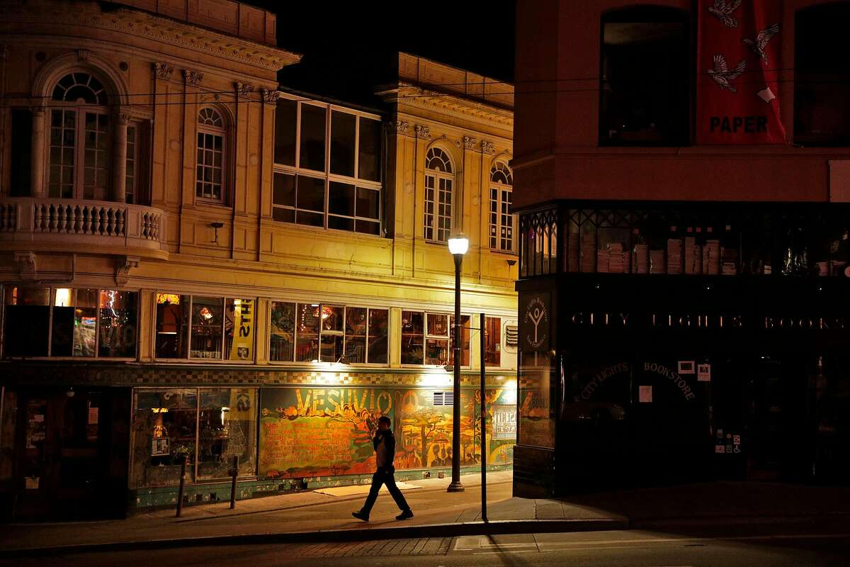 A pedestrian walks by darkened North Beach mainstays Cafe Vesuvio and City Lights Bookstore as the city began to shut down following an order to shelter in place in San Francisco, Calif., on Monday, March 16, 2020. The six Bay Area counties issued a shelter in place order for residents to try and curtail the spread of the Covid-19 virus.