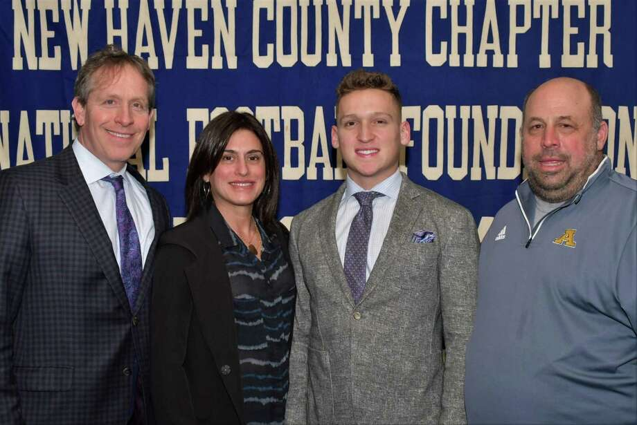 Amity's Samuel Sachs has been named a scholar athlete by the Casey-O'Brien New Haven County Chapter of the National Football Foundation and College Hall of Fame. He is pictured with his parents Greg and Lisa (L) and coach Craig Bruno. Photo: Submitted / Bill O'Brien
