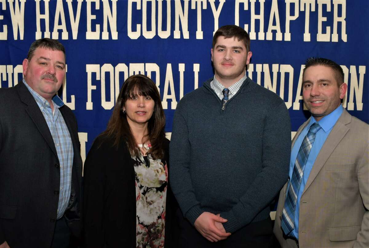 Ansonia's Garrett Cafaro has been named a scholar athlete by the Casey-O'Brien New Haven County Chapter of the National Football Foundation and College Hall of Fame. He is pictured with his parents Laurence and Lisa (L) and coach Thomas Brockett.