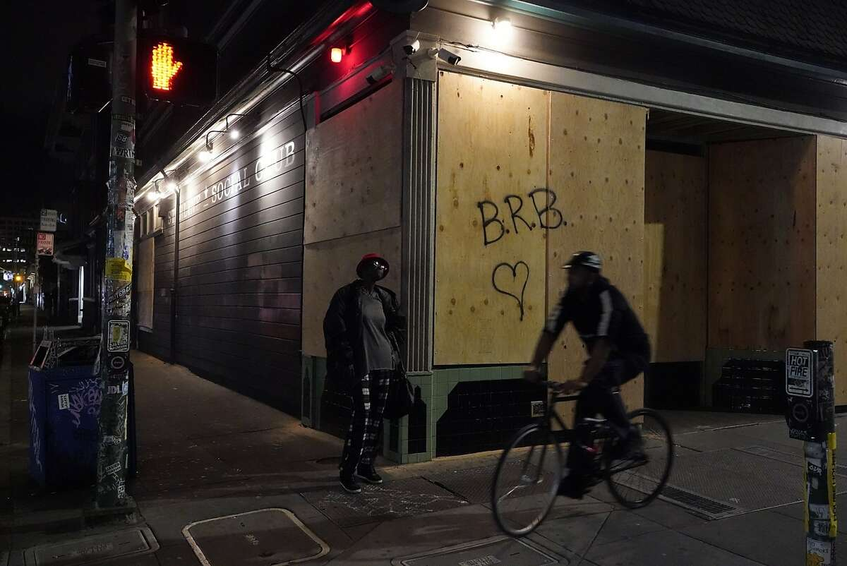 Jennifer Vaughn pose in front of the Starline Social Club she used to attend but now is boarded up due to the lockdown on Monday, March 16, 2020, in Oakland, Calif..