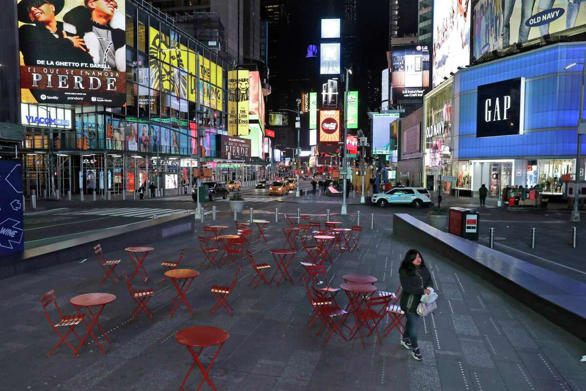A woman walks through a lightly trafficked Times Square in New York, Monday, March 16, 2020. Bars and restaurants will become takeout-only and businesses from movie theaters and casinos to gyms and beyond will be shuttered Monday night throughout New York, New Jersey and Connecticut because of the coronavirus, the states' governors said.