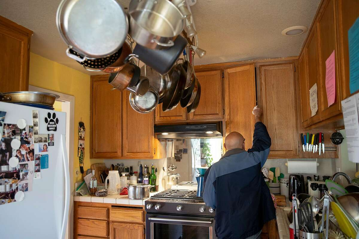 David Stahlberg wipes down his kitchen on Friday, March 13, 2020, in Cotati, Calif. Stahlberg returned from Italy with his wife. His wife became ill with what her doctor thinks is COVID-19.
