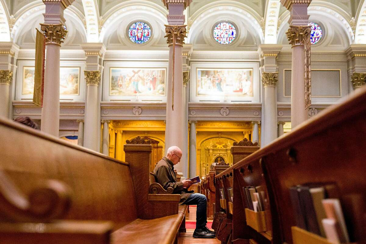 Tom Whelan of San Francisco sits by himself in a pew as he reads his personal bible while attending morning mass service at St. Ignatius Church in San Francisco, Calif. Friday, March 13, 2020. Friday's morning mass was moved from a smaller side parish to the main parish to help those worshipping keep their distance from one another amid the global thread of the Coronavirus.