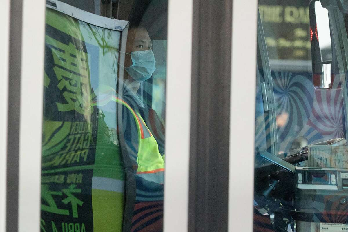 A San Francisco MUNI bus driver wears a protective mask while working during rush hour in San Francisco.