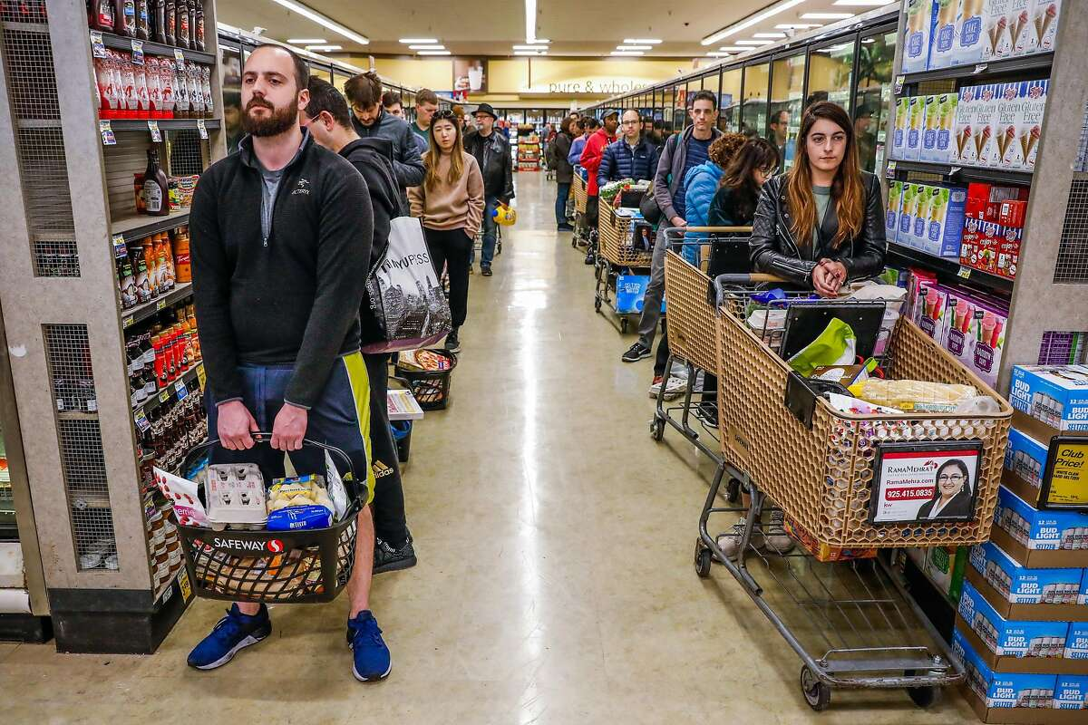 Vinny Verdeschi (left) and Liz Roland (right) wait in line at Safeway after Mayor London Breed announced that six Bay Area counties would lockdown non-essential services due to the coronavirus on Monday, March 16, 2020 in San Francisco, California.