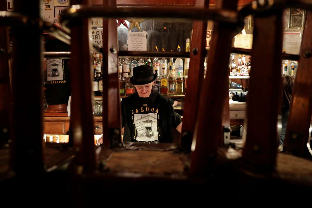 Spark the bartender, cleans up at The Saloon after closing as the city began to shut down following an order to shelter in place in San Francisco, Calif., on Monday, March 16, 2020.