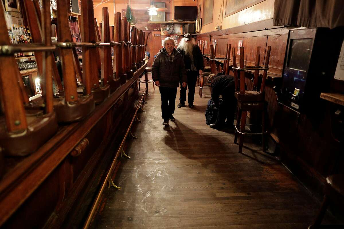 Myron Mu, owner of The Saloon, walks toward the exit after closing as the city began to shut down following an order to shelter in place in San Francisco, Calif., on Monday, March 16, 2020.