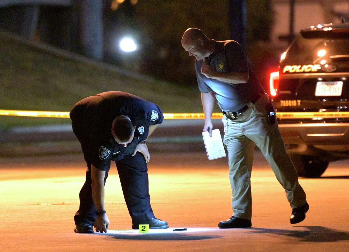 Police look at a machete while they investigate the scene where an officer shot a man who was pulled over for a traffic infraction in the 1100 block of South Laredo Street.