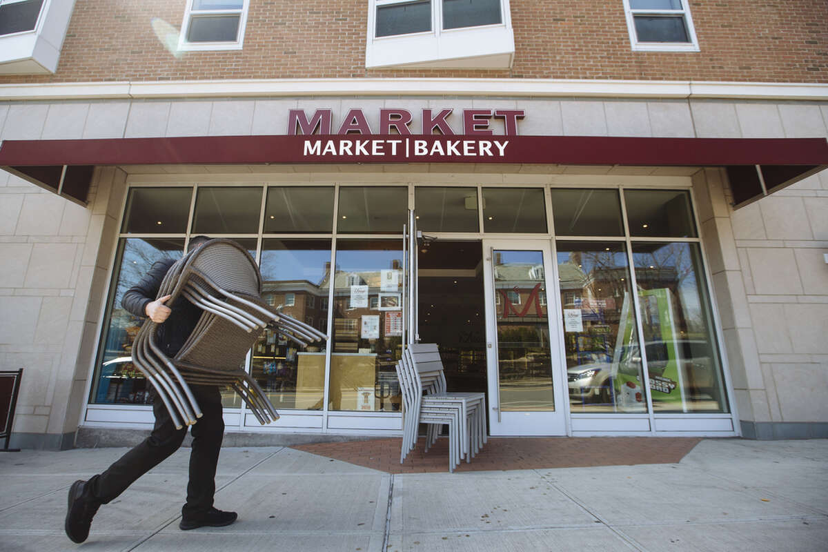 An employee carries chairs outside of a market in New Rochelle, New York, U.S., on Monday, March 16, 2020. The governors of New York, New Jersey and Connecticut banned all gatherings of 50 or more people, and said bars, restaurants, casinos and gyms must close Monday at 8 p.m. Photographer: Angus Mordant/Bloomberg
