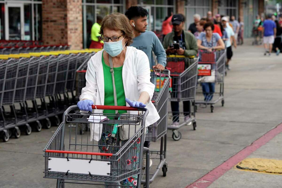Ruth Flavelle wears a mask and gloves as she enters an H-E-B grocery after waiting in line with more than 150 people Tuesday, March 17, 2020, in Spring, Texas. Grocery stores across the country have started to reserve special hours for older, at-risk Americans during the coronavirus pandemic.