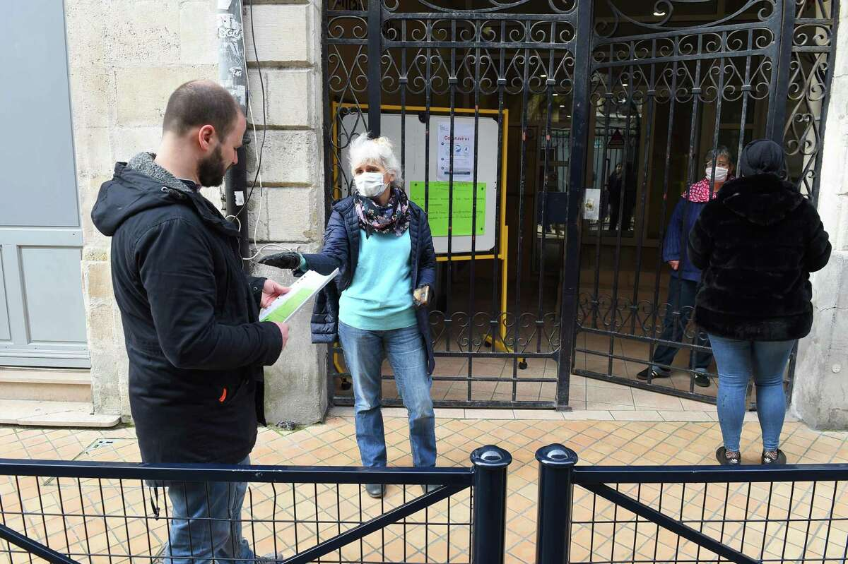 Teachers of an elementary school, wearing a protective facemask, give instructions to a parent about homework of children, on March 17, 2020 in Bordeaux, southwestern France.
